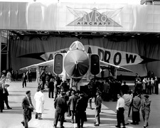 After four years of work by 14,000 people, the first Avro Arrow is wheeled out of a hangar in Malton, Ontario, on 4 October 1957. A huge crowd is on hand to marvel at the sleek white craft. (Canadian Department of National Defence)